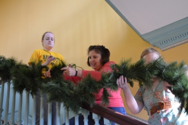 Curatorial staff attach the greenery to the banister.