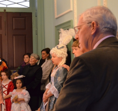 Visitors, some who came dressed in colonial-era clothing, join in the singing.