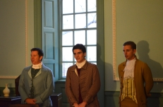(l-r) John Lewis (Michael Taylor) and George Lewis (Will Goldstein), two of Fielding Lewis's sons, are joined by Captain Richard Taylor (Scott Houk) , a local ship's master, in the singing of a traditional carol.