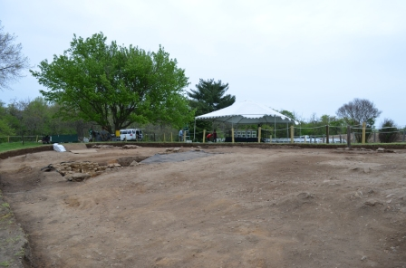The large area of dirt encompasses the Washington House's location. Preparations for the groundbreaking take place in the background.