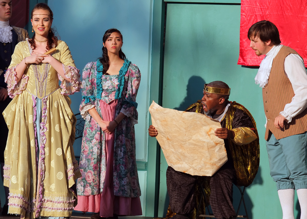 King Lear (Marcus Salley - center) decides to divide his kingdom among his three daughters but demands they declare how much they love him first. Goneril (Corinn Keene - far left) makes her disingenuous declaration.