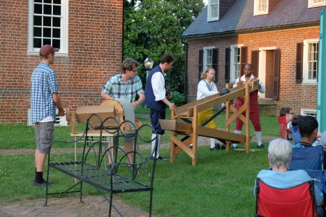 Cast and support staff operate 18th-century sound effect machines to create rain, wind, and thunder for the dramatic storm scene.