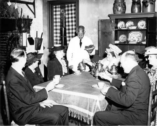 Visitors enjoy tea and gingerbread in the kitchen. Several pieces of the china displayed in the cupboard in the background and the cupboard itself have been returned to the kitchen.