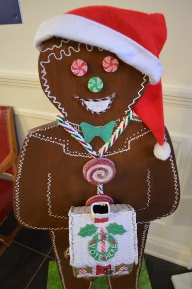 Mr. Gingerbread happily accepts votes for favorite gingerbread house.