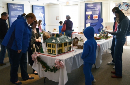 Visitors view the gingerbread houses during Sunday's opening reception.