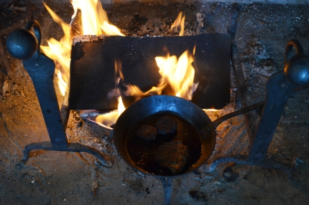 Sausage cooking over the fire in the kitchen.