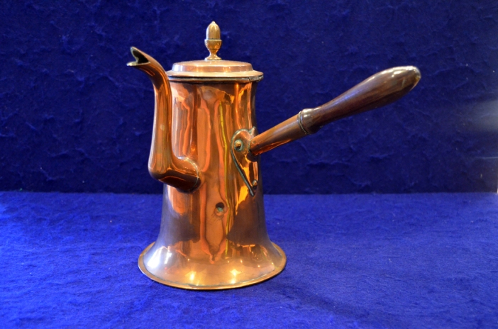 "This cooper chocolate pot features a wooden handle, ""Goose neck"" spout with split tip, a hinged lid with inverted acorn-shaped knob, and a tinned interior."
