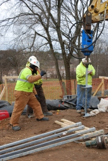 Workers drill helical piles as part of the special concrete cradle the house will rest on.