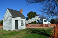 """A dump truck passes the 19th century building mistaken for George Washington's """"Surveyor's Shed"""" as it lays gravel for an access road to the construction site."""