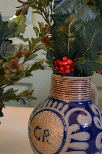 A replica Westerwald jug containing holiday greenery inside Kenmore.