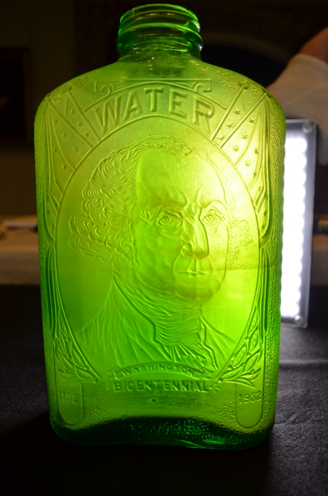 "A green water bottle with a likeness of George Washington under the word ""water."" The bottle reads ""Washington / Bicentennial"" with the dates 1732 and 1932 on either side. It was made by the Hemingray Glass Company in Muncie, Indiana."