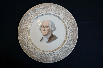 A commemorative plate from 1932 with an elaborate floral gilded border and a transfer-printed bust of George Washington in the center and made by the Capital Souvenir Company.