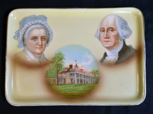 "A commemorative porcelain tray depicting George Washington, Martha Washington, and Mount Vernon. The vignettes were transfer-printed first and then hand-painted to add details. At the bottom of the Mount Vernon vignette is printed ""Washington's Home / Mount Vernon, Va."" The tray was made by Tressemann & Vogt in Germany between 1891 and 1907."