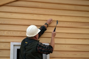Carpenter Tom Rainey hammers a nail into the weatherboard.