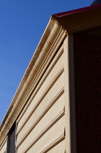 Weatherboard and the decorative rake board at the base of the roof beaded with dew.