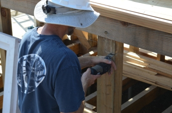 Carpenter Josh Schwenk notches out a timber where the frame will rest.