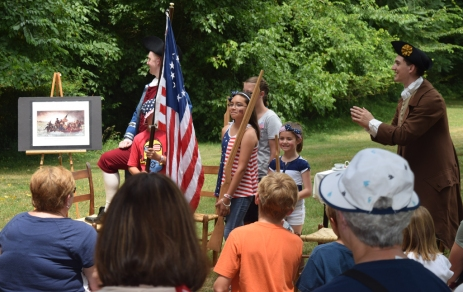 Audience members recreate the painting of Washington crossing the Delaware.