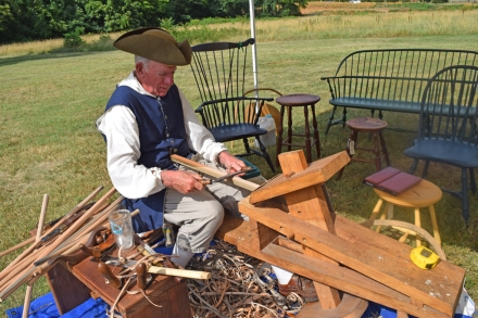 Artisan Bill Jenkins uses a draw knife to craft part of a Windsor chair.