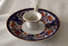 "A porcelain chamberstick, probably made in the 1970s or 1980s to mimic a colonial style. The decoration on this one is what really caught our eye – the blue and orange-red enamel with gilt highlights is known as the ""Imari"" palette and was often found on Chinese Export Porcelain teawares in the Washingtons' time."