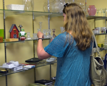 Ceramics and Glass Specialist Mara Kaktins examines some glass candlesticks for historical accuracy.
