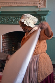 Rachel, an enslaved cook (Gladys Perkins), clears the dining room table after the ball's grand meal is complete.