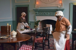 Ashlee James as Rachel, the washerwoman (L), and Gladys Perkins as Hetty, the cook (R), talk about the wisdom of running away to freedom promised by the British.