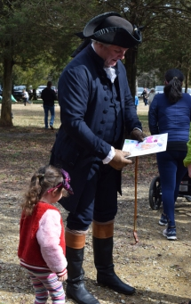 A young visitor presents a birthday card she made to Geroge Washington.
