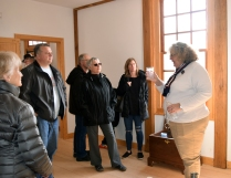 Washington house guide Carole White encourages visitors to examine the reproduction 18th century objects in the house.